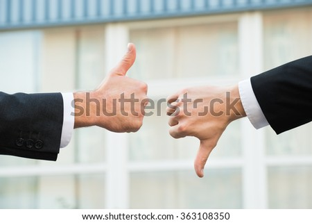 Cropped hands of businessmen showing like and dislike signs outdoors - stock photo