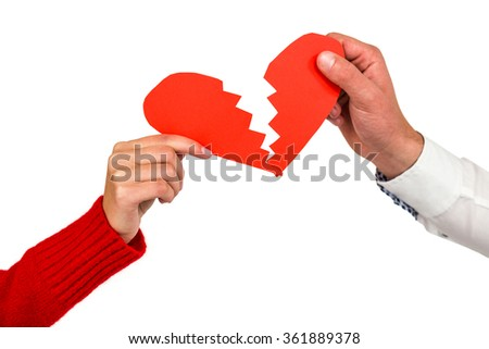 Cropped hands of couple holding red cracked heart shape over white background - stock photo