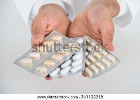 Cropped hands of doctor holding blister packs against white background - stock photo