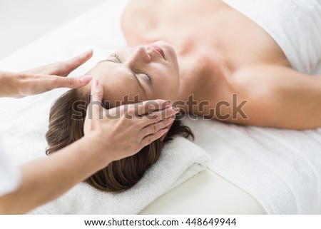 Cropped hands of therapist performing reiki on woman at spa - stock photo