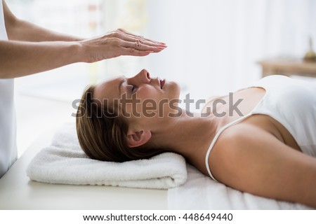 Cropped hands of therapist performing reiki on young woman at spa - stock photo