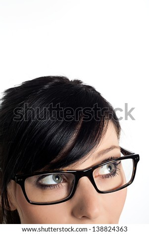 Cropped image a young woman's face with her eyes looking at corner against white background