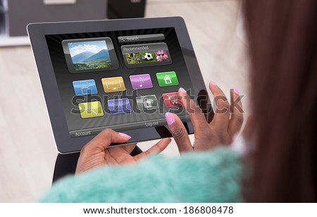 Cropped image African American woman using digital tablet at home - stock photo