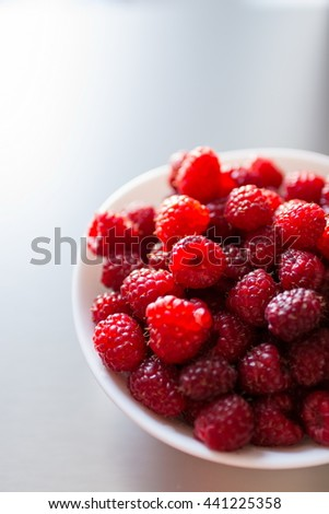 Cropped image of a beautiful selection of freshly picked ripe red raspberries in the white bowl on a metal background - stock photo