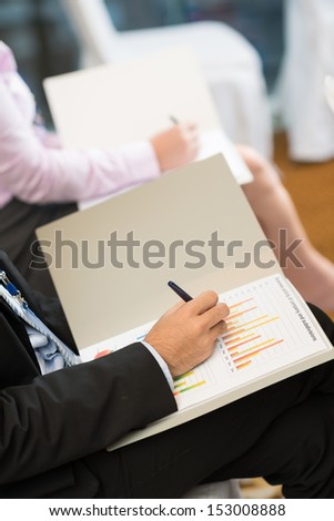 Cropped image of a businessperson working with business graphic on the foreground - stock photo