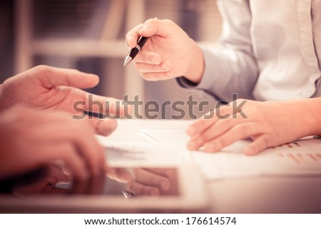 Cropped image of a businesswoman holding a pen and pointing at something while dealing with her colleague on the foreground  - stock photo