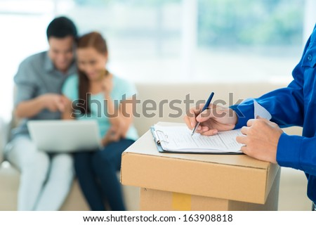 Cropped image of a delivery man fill in the application form on the foreground - stock photo