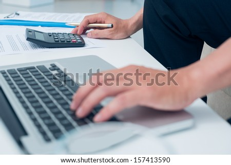Cropped image of a financial consultant counting something using a calculator and a laptop on the foreground