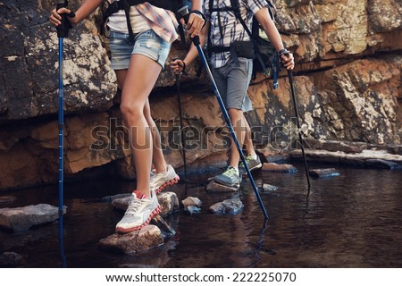 Cropped image of a hiking woman and man crossing a dam by balancing on the rocks in the dam - stock photo