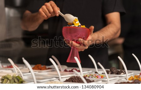 Cropped image of a man decorating ice-cream with gems and jellies.
