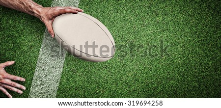 Cropped image of a man holding rugby ball against pitch with line - stock photo