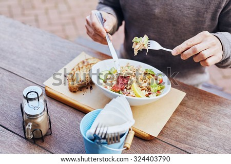 Cropped image of a man on his lunch break eating a fresh and healthy salad with chicken, avocado, sundried tomatoes and fresh sliced baguette on the side while sitting at a wooden table - stock photo