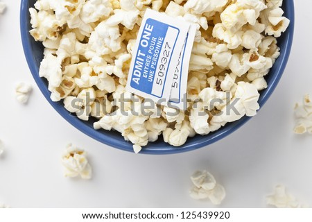 Cropped image of a popcorn bowl with movie tickets placed in a white background with popcorn spills - stock photo