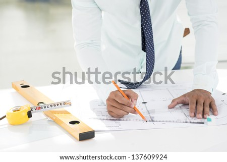 Cropped image of a professional draftsman correcting a blueprint - stock photo