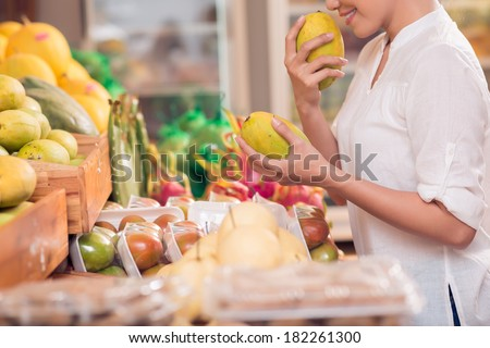 Cropped image of a woman choosing fresh mango fruit in the grocery shop on the foreground  - stock photo