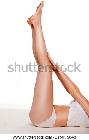 Cropped image of a woman doing yoga lying on her back with her bare tanned shapely legs straight up in the air - stock photo