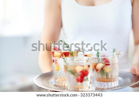 Cropped image of a woman holding a tray of cocktails, mocktails, refreshing drinks with garnish, raspberries and sliced apple in them