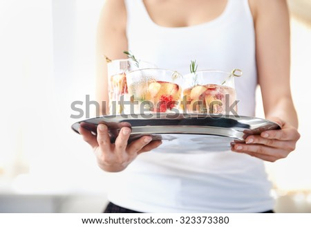 Cropped image of a woman holding a tray of refreshing cold drinks with fresh fruit garnishes in them - stock photo