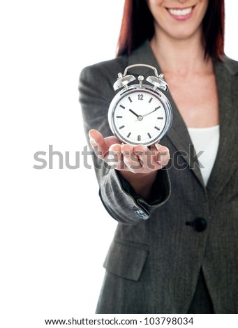 Cropped image of a woman holding alarm clock. Studio shot