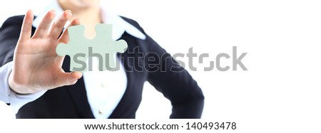 Cropped image of a woman in a business suit holding a single jigsaw piece - stock photo