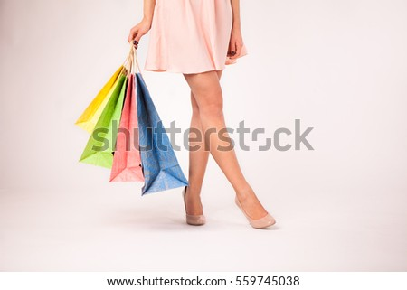 Cropped image of a woman in pink dress  holding colorful shopping bags  on a white background