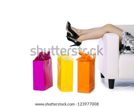 Cropped image of a woman lying on couch with shopping bags on the side over white background - stock photo