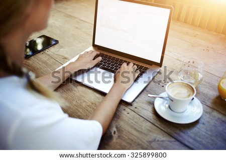 Cropped image of a woman's hands keyboarding on net-book while sitting at the wooden table in cafe, female student working on laptop computer with copy space screen background for your text message