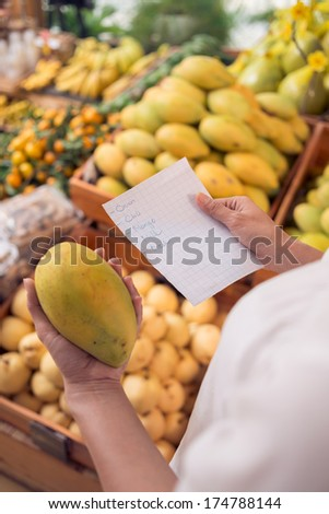 Cropped image of a woman shopping in the market according the shopping list  - stock photo