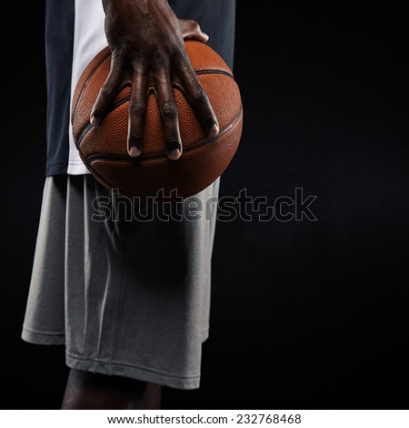 Cropped image of a young man holding basketball against black background. Mid section image of african basketball player holding ball. Focus on hand. - stock photo