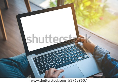 Cropped image of a young man working on his laptop in a coffee shop, rear view of business man hands busy using laptop at office desk, typing on computer sitting at wooden table