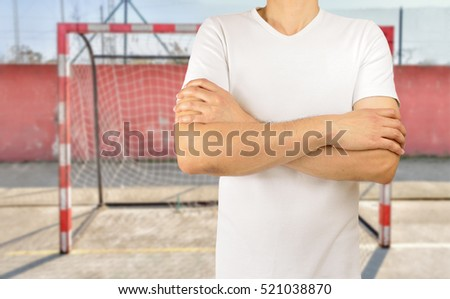 cropped image of a young soccer player with crossed arms wearing white tshirt at empty football court in background