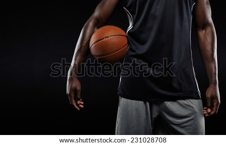 Cropped image of afro american basketball player holding a ball against dark background - stock photo