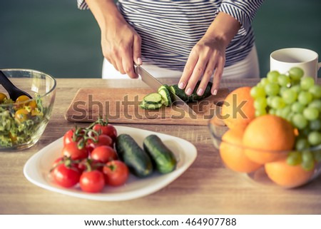 Cropped image of attractive girl cutting cucumber while making salad in her kitchen at home