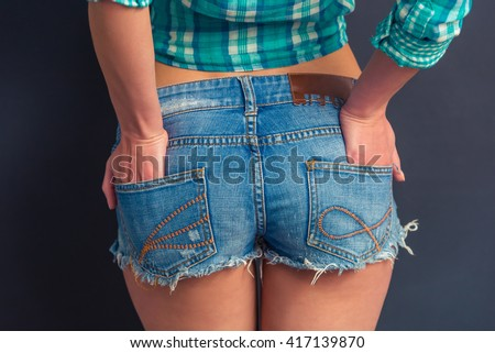 Cropped image of attractive girl in jeans shorts standing with hands in back pockets against dark background - stock photo