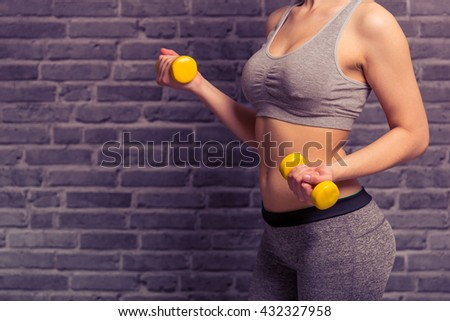 Cropped image of attractive young woman in sportswear holding dumbbells, against brick wall - stock photo