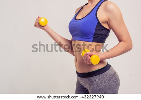 Cropped image of attractive young woman in sportswear holding dumbbells, on a gray background - stock photo