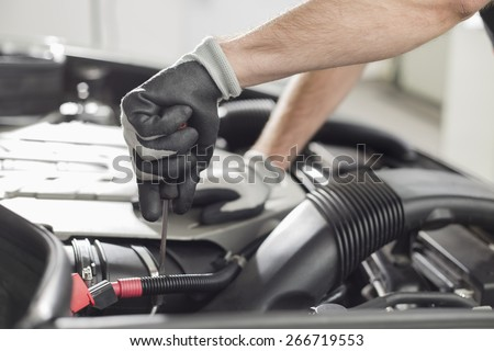 Cropped image of automobile mechanic repairing car in automobile store