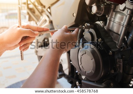 Cropped image of automobile mechanic repairing motorcycle in automobile store