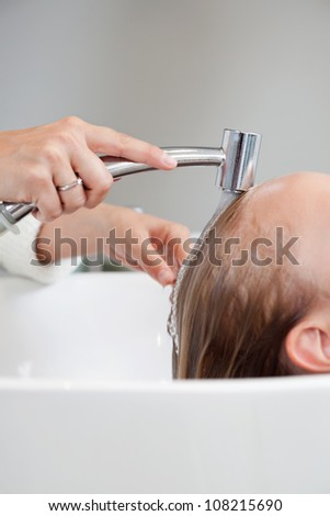 Cropped image of beautician washing hair of female customer at beauty salon