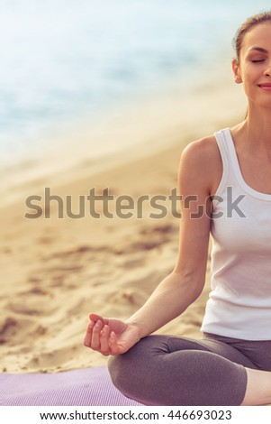 Cropped image of beautiful girl in sport clothes meditating and smiling while sitting in lotus position on yoga mat on the beach