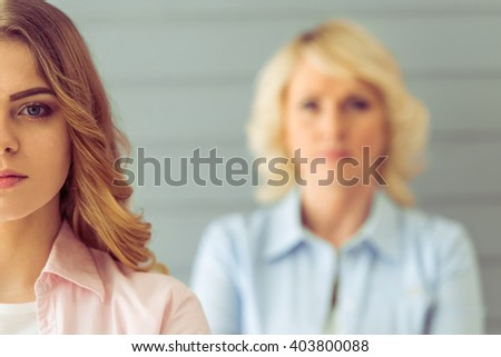 Cropped image of beautiful mature mother and her daughter looking at camera, standing one by one against gray background - stock photo