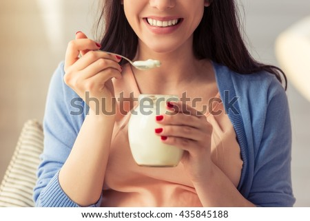 Cropped image of beautiful pregnant woman eating yogurt and smiling while sitting at home