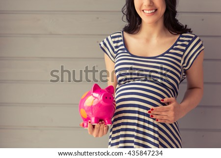 Cropped image of beautiful pregnant woman holding a piggy bank, keeping one hand on a belly and smiling, standing against gray wall - stock photo