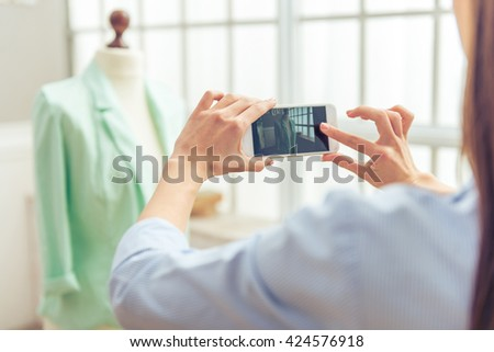 Cropped image of beautiful young designer taking photo of her work using a smartphone, in dressmaking studio - stock photo