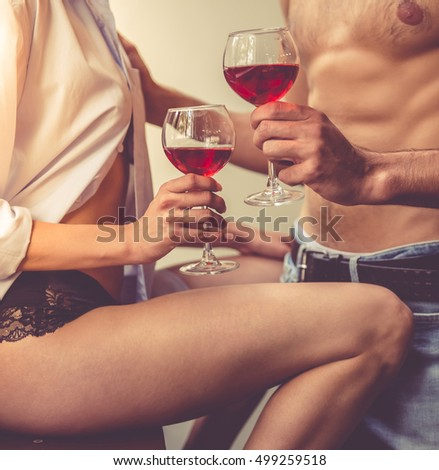 Cropped image of beautiful young passionate couple drinking wine in kitchen at home