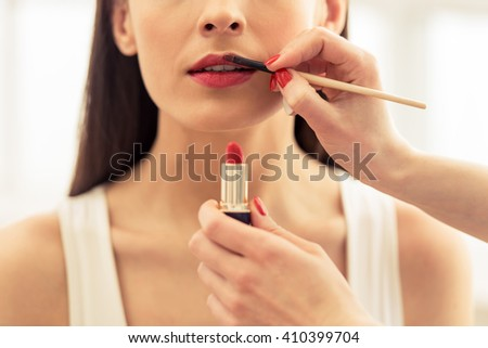 Cropped image of beautiful young woman, visagiste is doing her makeup and holding a lipstick - stock photo