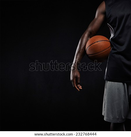 Cropped image of black basketball player standing with a basket ball. Man in sportswear holding basketball with copyspace on black background. - stock photo
