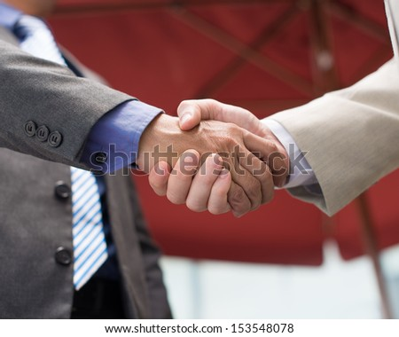 Cropped image of business colleagues handshaking as a sign of agreement on the foreground - stock photo