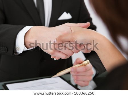 Cropped image of business colleagues shaking hands at desk - stock photo