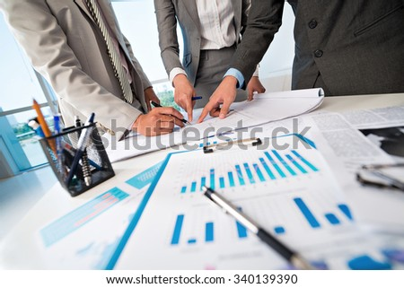 Cropped image of business people discussing blueprint